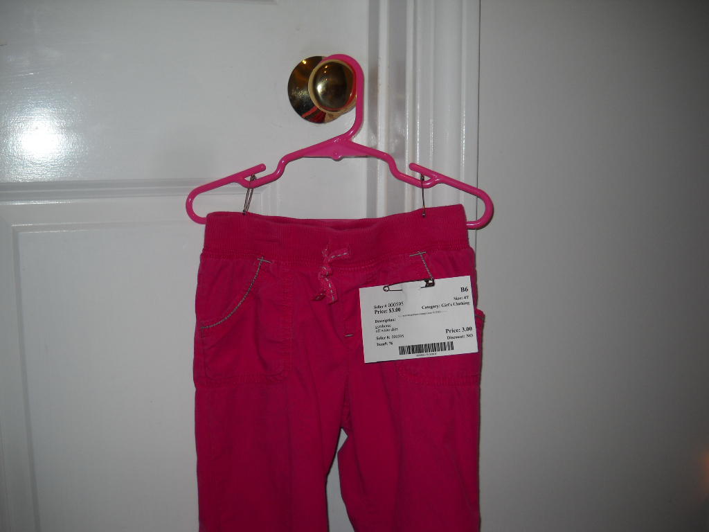 Pants on hanger with hook opening facing left, like a question mark